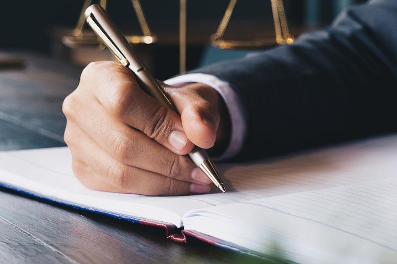 Mężczyzna piszący piórem nakartce